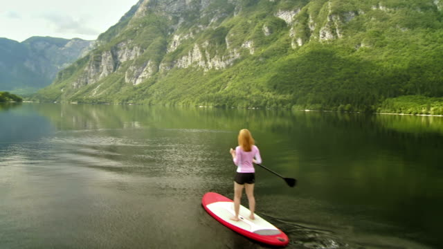 stockvideo's en b-roll-footage met woman stand up paddle surfing - peddelen