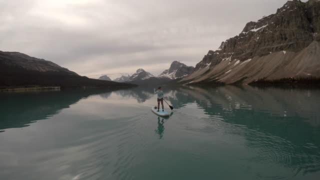 woman stand up paddleboards across mountain lake - pedal pushers stock videos & royalty-free footage