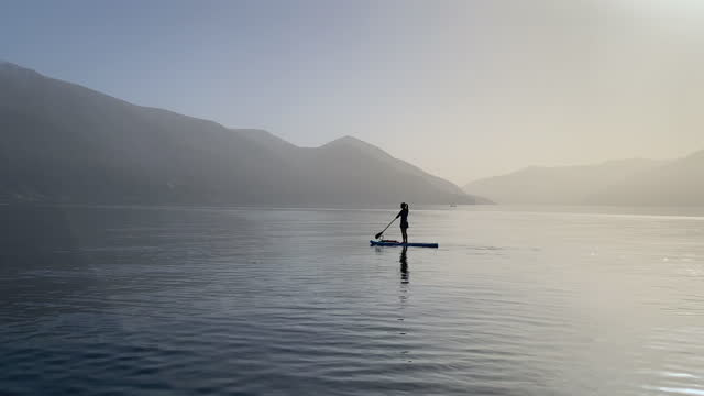 woman stand up paddling sup on calm lake at sunset under snow capped mountains - paddel stock-videos und b-roll-filmmaterial