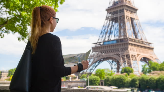 woman standing across from eiffel tower, exploring paris with map - opportunity stock videos & royalty-free footage