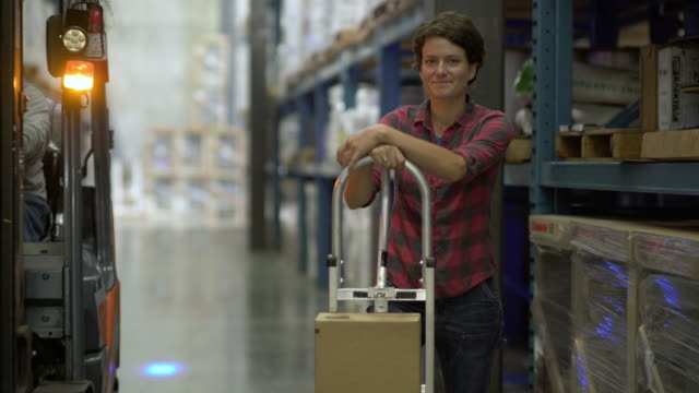 Woman standing and leaning on trolley with boxes, looking at camera and smiling