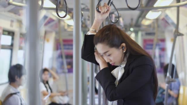 女性は立っていると、電車の中で昼寝します。 - exhaustion点の映像素材/bロール
