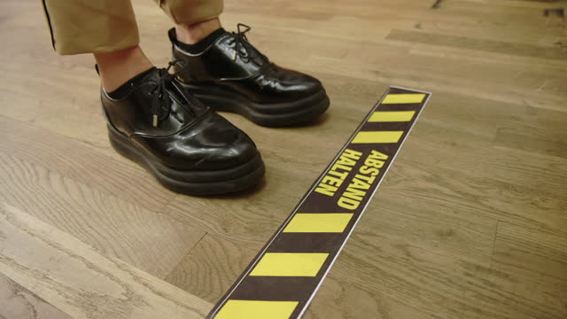 woman standing at warning sign on floor in store - low section stock videos & royalty-free footage