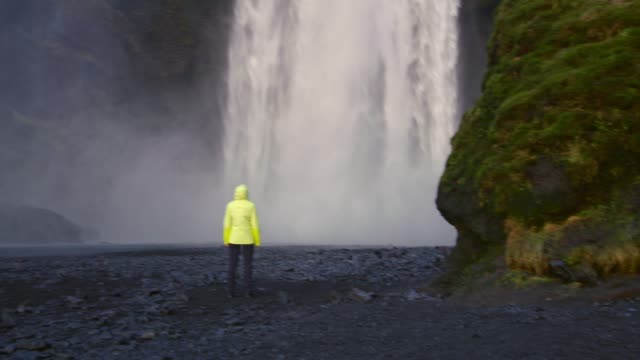 ms woman standing below waterfall,iceland - concepts stock videos & royalty-free footage