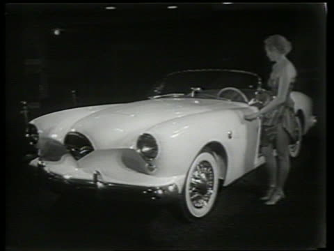 vidéos et rushes de woman standing by kaiser darrin sports car on display at car show / sound - voiture particulière