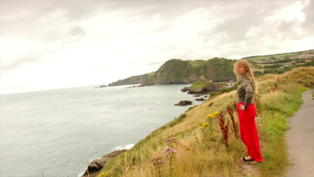 woman standing by the sea in england - devon stock videos & royalty-free footage