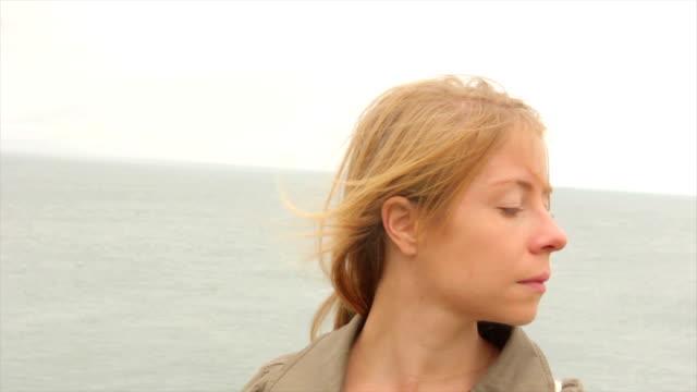 Frau stehend am Meer in England
