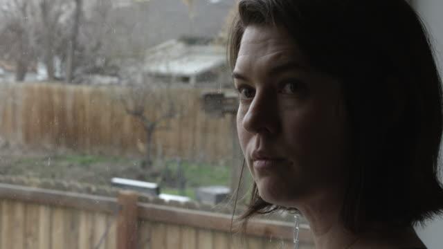woman standing by window turning her head - プロボ点の映像素材/bロール