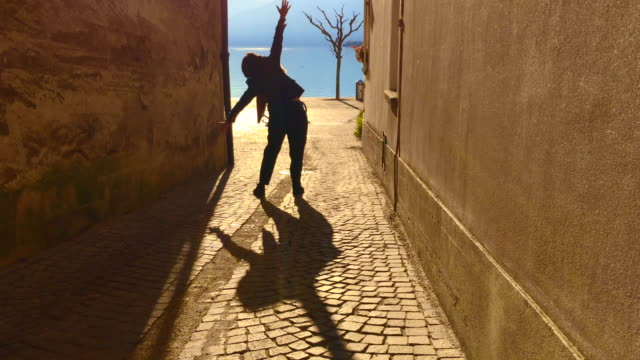 Woman Standing in a Narrow Street and Moving Her Arms Outstretched with Shadow