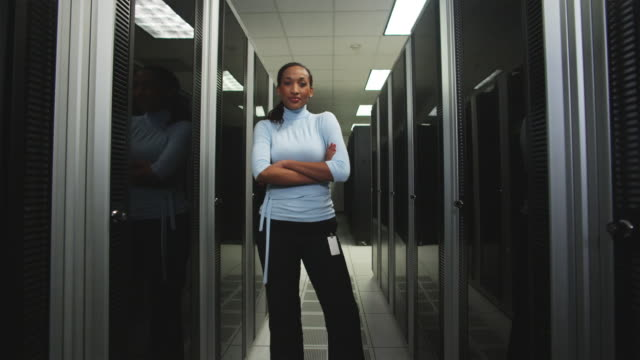 woman standing in a server room - netzwerkadministrator stock-videos und b-roll-filmmaterial