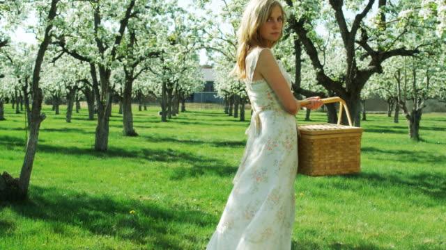 vídeos de stock e filmes b-roll de woman standing in an orchard with a picnic basket - só uma menina adolescente
