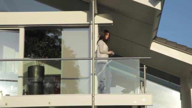 ws tu td pan woman standing in balcony, drinking coffee / kleinmachnow, brandenburg, germany - balkon stock-videos und b-roll-filmmaterial