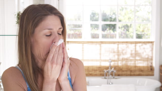 ms woman standing in bathroom sneezing into tissue, phoenix, arizona, usa - allergy stock videos & royalty-free footage