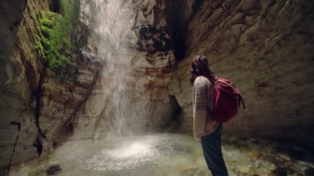 vídeos de stock e filmes b-roll de woman standing in cave and looking at waterfall - cascata