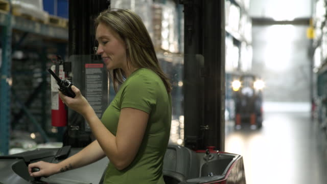 Woman standing in forklift machinery, talking through hand held radio system, background people