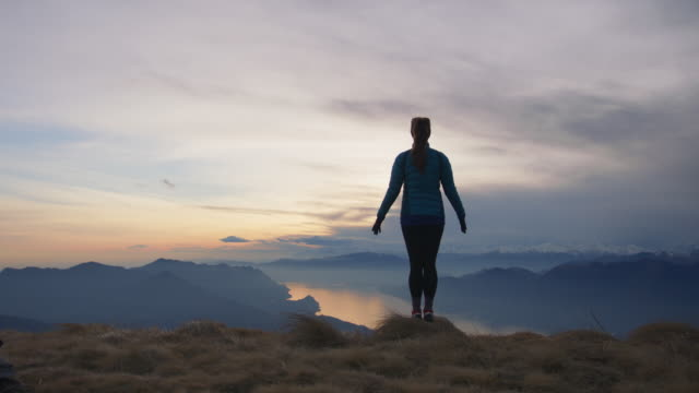 woman standing in freedom pose at the top of a mountain - arms outstretched stock videos & royalty-free footage