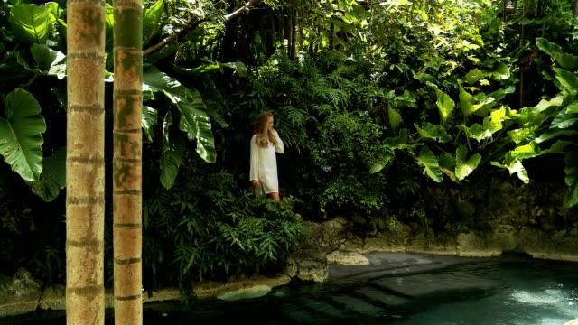 vidéos et rushes de femme debout devant une piscine tropicale - robe blanche