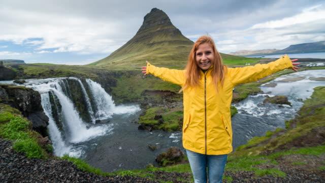 vídeos y material grabado en eventos de stock de mujer de pie delante de kirkjufell montaña en islandia - volcán extinguido