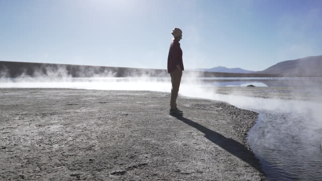 woman standing in front of steaming hot lake in the andean mountains - geysir stock-videos und b-roll-filmmaterial