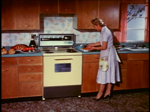 1958 woman standing in kitchen examining cooked food on countertop near oven - hausfrau stock-videos und b-roll-filmmaterial