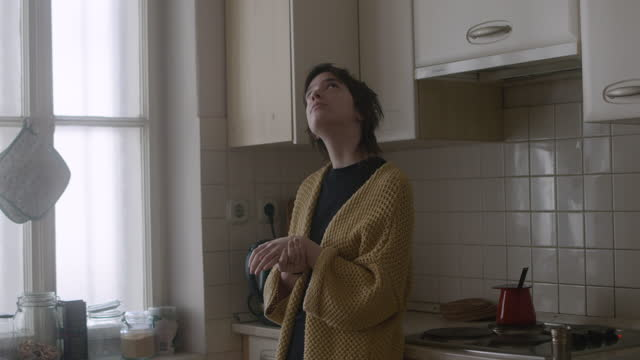 woman standing in kitchen feels some pain in her wrist - grief stock videos & royalty-free footage