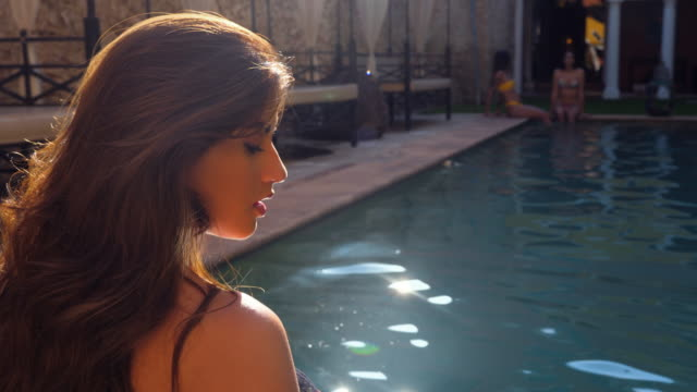 ts woman standing in pool in courtyard of hotel while friends sit on edge - poolside stock videos & royalty-free footage