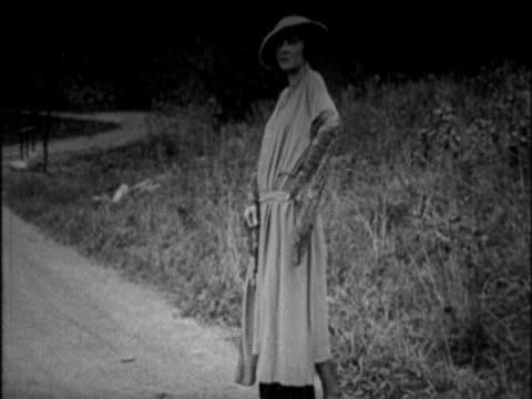 b/w 1925 woman standing in road modeling dress + looking at camera / newsreel - 1925 stock videos & royalty-free footage