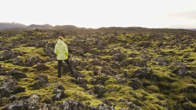 vídeos de stock, filmes e b-roll de mulher da senhora que está na paisagem áspera, remota, islândia - musgo