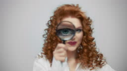 Woman standing in studio with magnifier glass in hand. Lady having fun