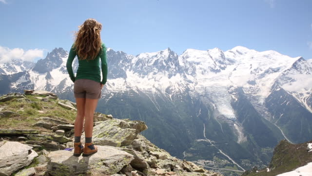 vidéos et rushes de a woman standing in the mountains of the alps as the wind blows through her hair. - haut
