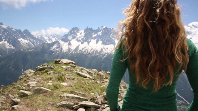 a woman standing in the mountains of the alps as the wind blows through her hair. - blond hair stock videos & royalty-free footage