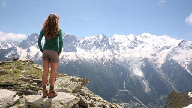 a woman standing in the mountains of the alps as the wind blows through her hair. - top garment stock videos and b-roll footage