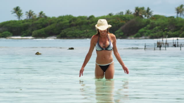 woman standing in the ocean - isola di tahaa video stock e b–roll