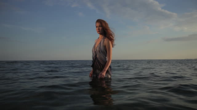 ms woman standing in the sea water moving around her and wind blowing hair. - wind stock videos & royalty-free footage