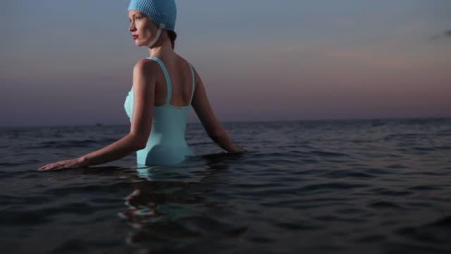 ms woman standing in the sea wearing swimming hat. - swimming cap stock videos and b-roll footage