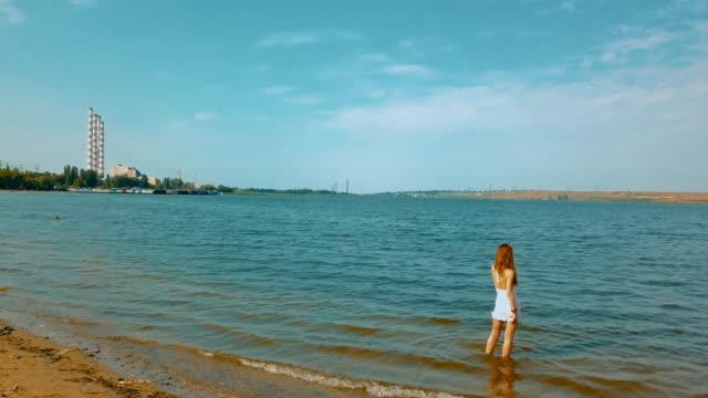 vídeos de stock, filmes e b-roll de mulher em pé na água admirando a vista - ficando de pé