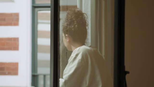 woman standing in window - hair bun stock videos & royalty-free footage