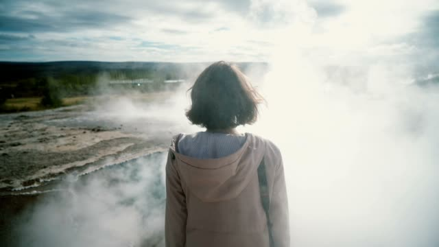 vídeos de stock e filmes b-roll de woman standing near the geyser in iceland - estupefação