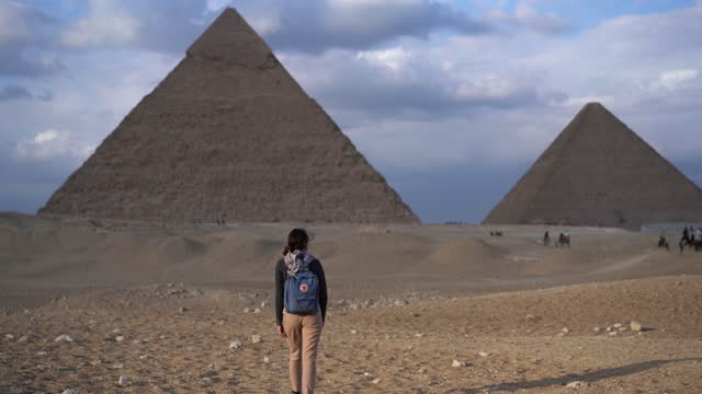 woman standing near the giza pyramids - stone object stock videos & royalty-free footage