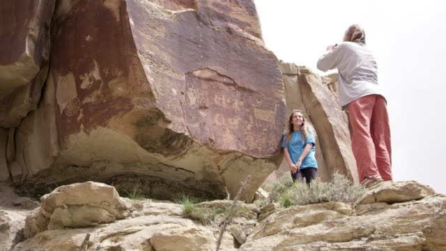 woman standing next to petroglyphs as another takes picture - anasazi stock videos & royalty-free footage