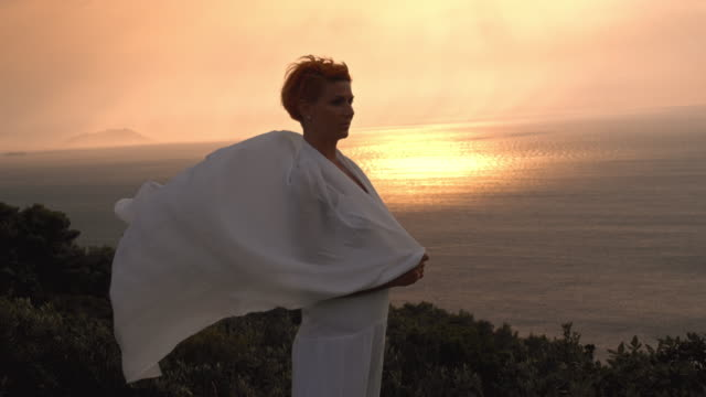 slo mo woman standing on a cliff at sunset - shawl stock videos and b-roll footage