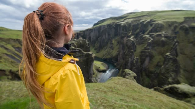 woman standing on a cliff, looking down at iceland's canyon - viewpoint stock videos and b-roll footage