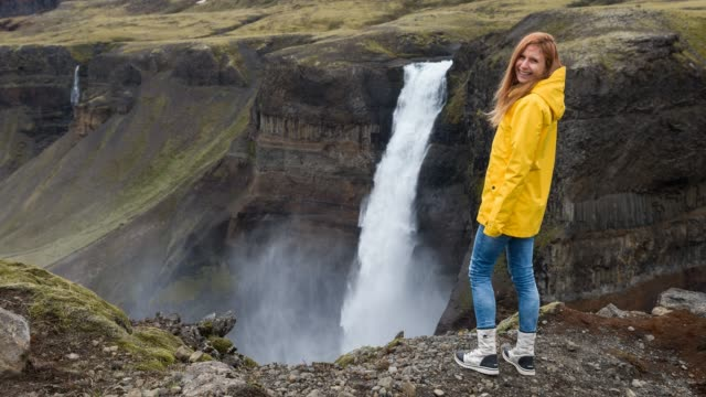woman standing on a cliff, looking down at waterfall - cliff stock videos & royalty-free footage
