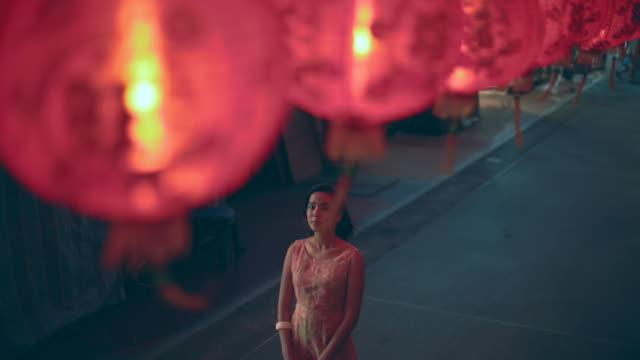 stockvideo's en b-roll-footage met ws woman standing on a street, under red lanterns. - chinees nieuwjaar