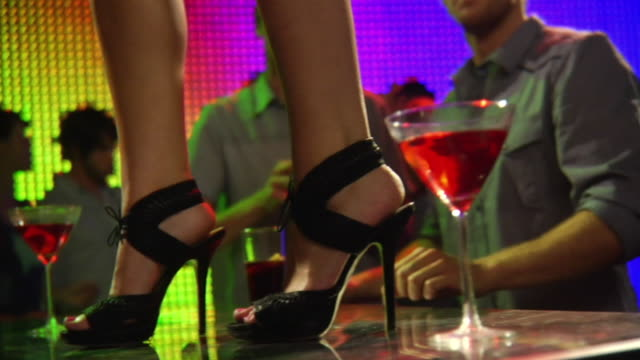 MS SLO MO ZI Woman standing on bar in stiletto shoes / London, UK