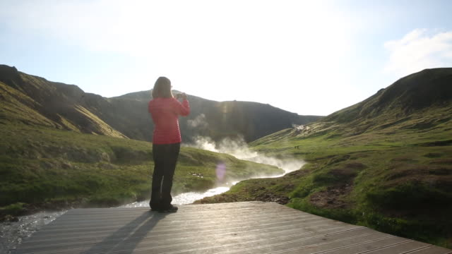 woman standing on boardwalk taking a picture of a hot spring in iceland - hot spring stock videos & royalty-free footage