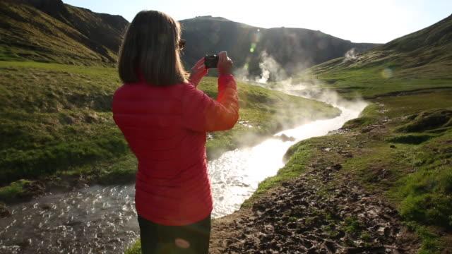 vídeos y material grabado en eventos de stock de woman standing on boardwalk taking a picture of a hot spring in iceland - fotografía temas