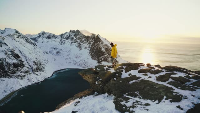 woman standing on cliff and lookin at seaside of lofoten island in snow - adventure stock videos & royalty-free footage