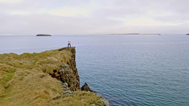vídeos de stock e filmes b-roll de ws woman standing on cliff overlooking ocean,iceland - penhasco caraterísticas do território
