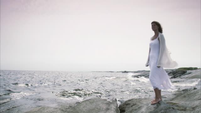 woman standing on cliffs by the sea huvudskar stockholm archipelago sweden. - solo una donna di età media video stock e b–roll